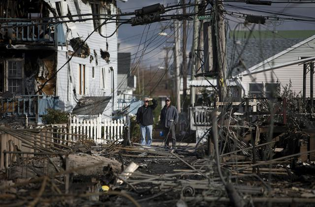 Residents look over the damage in the Breezy Point neighborhood of the Queens borough of New York in the wake of Atlantic superstorm Sandy. Photographer: Scott Eells/Bloomberg