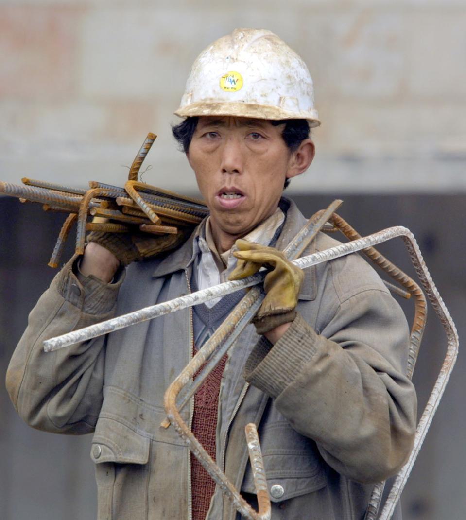 Un trabajador de la construcción transporta una carga de barras de refuerzo de acero en un sitio de construcción en Shanghai, China, el sábado 22 de marzo de 2003. Shanghai tenía el 40 por ciento de las grúas de construcción del mundo cuando Michael Wolley de BHP Steel Ltd. llegó en 1997. El boom de la construcción en China no se ha detenido y puede ayudar a la siderúrgica número 1 de Australia a superar su pronóstico de ganancias para 2003.  Fotógrafo: Kevin Lee / Bloomberg News