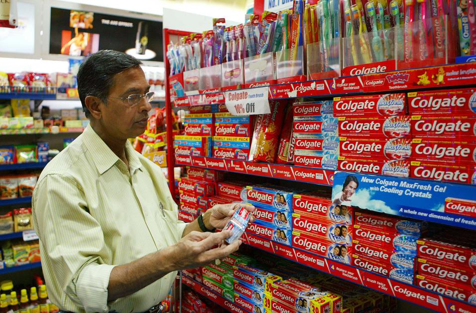 A shopper examines a box of Colgate toothpaste at a store in Mumbai, on Sunday, Jan. 21, 2007. Colgate - Palmolive India Ltd. third-quarter earnings are expected today. Photographer: Sebastian D'souza/Bloomberg News.