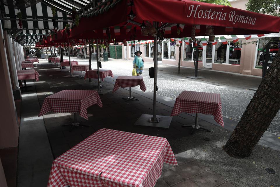 Empty tables at the Hosteria Romana restaurant in Miami Beach, Fla.