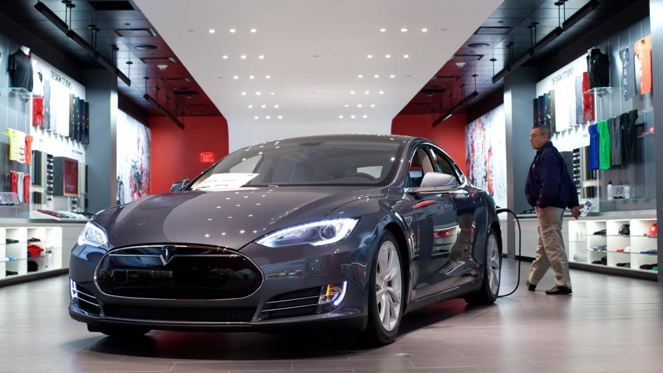 A Tesla Motors Inc. Model S connected to a charger sits on display at the company's store at the Short Hills Mall in Short Hills, New Jersey, Photographer: Emile Wamsteker/Bloomberg