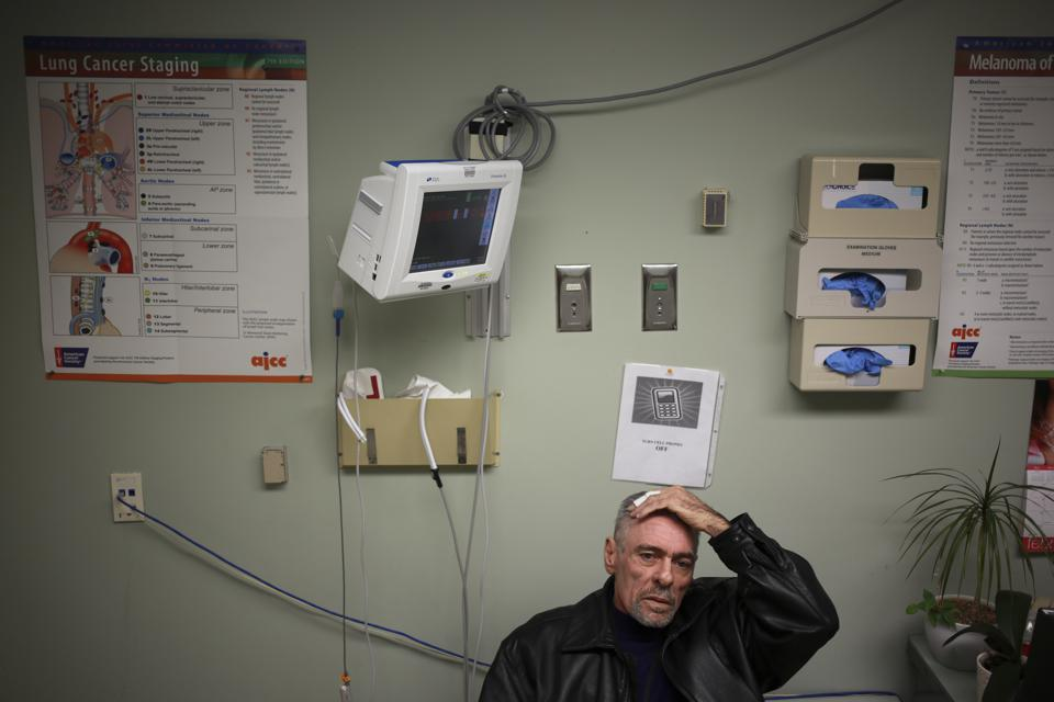 Cancer patient Tom Galjour sits in a waiting room during an appointment with his oncologist