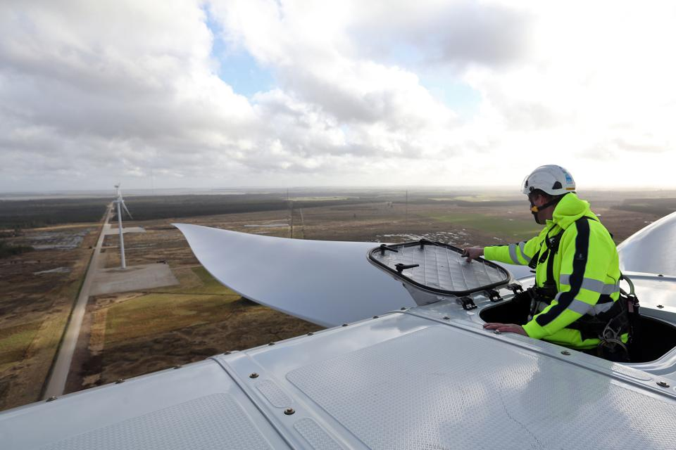 An employee prepares to climb onto the nacelle of a Vestas wind turbine in Denmark.