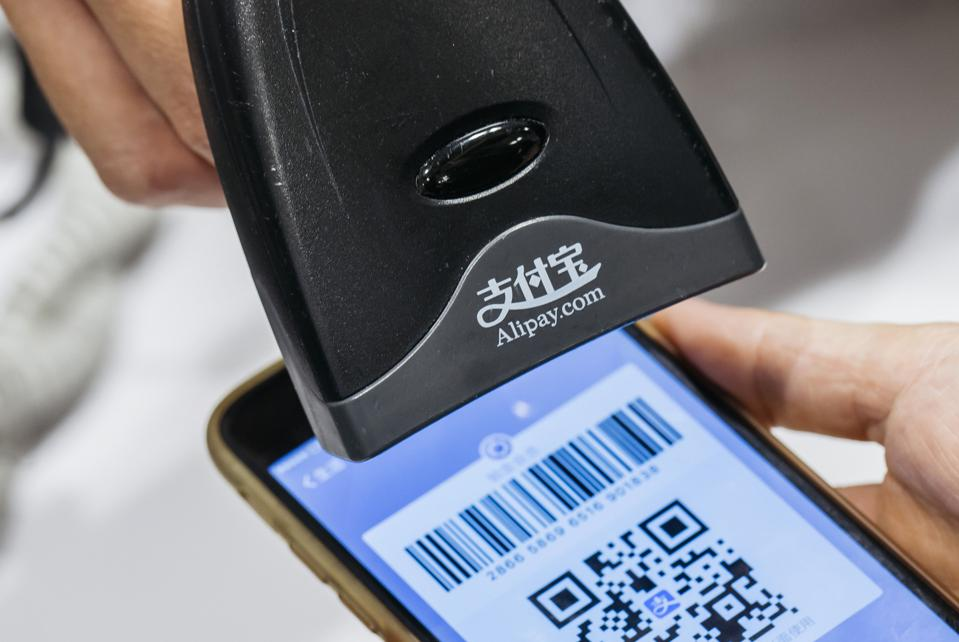 An employee scans a quick response (QR) code displayed on the Ant Financial Services Group's Alipay app.(Photo by Anthony Kwan/Bloomberg)