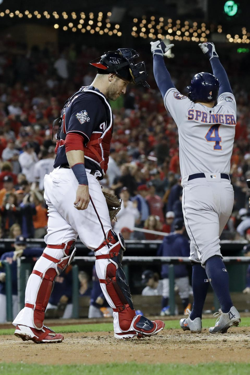 Houston Astros' George Springer celebrates past Washington Nationals catcher Yan Gomes after a two-run home run.