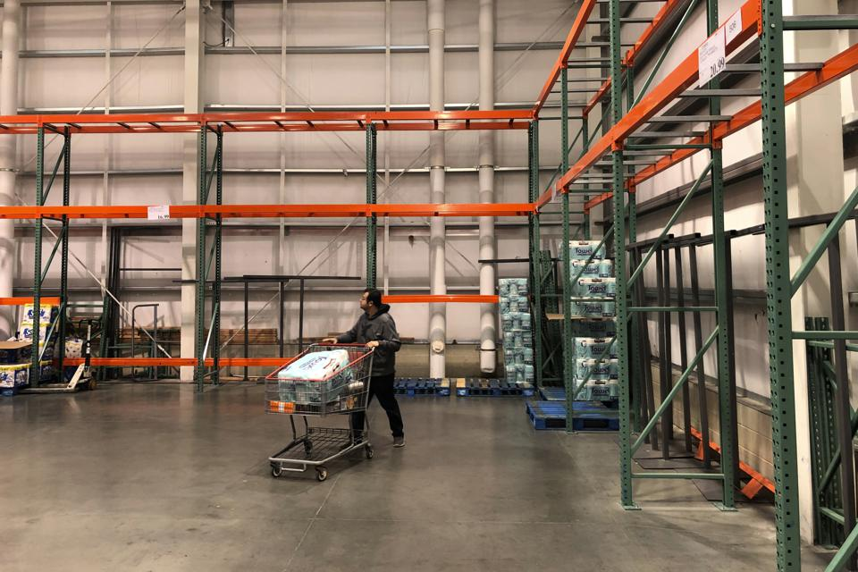 A customer walks past mostly empty shelves at a Costco store in Teterboro, N.J.