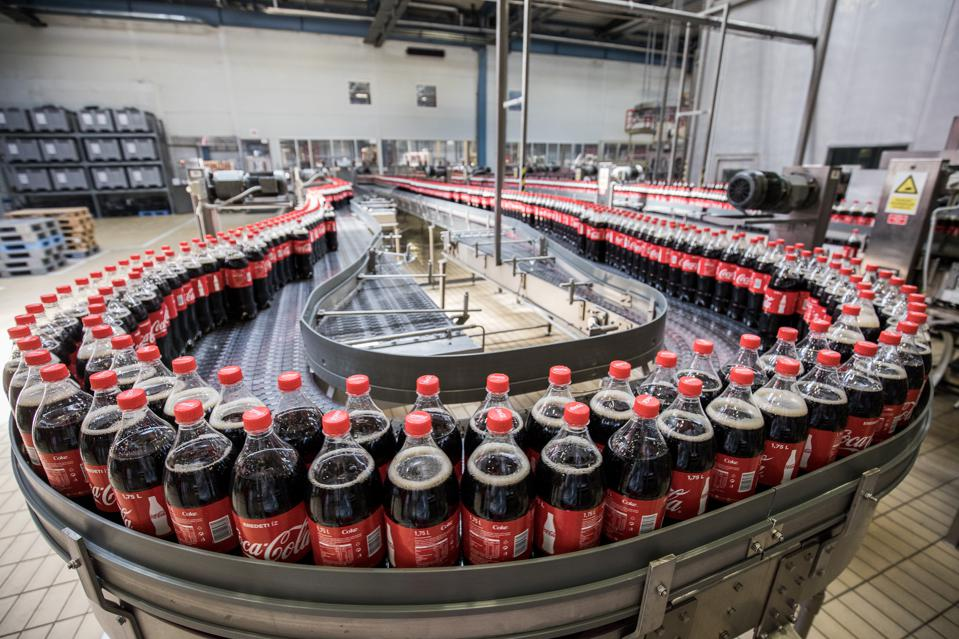 Plastic bottles of soda move along the automated production line.  Photographer: Akos Stiller/Bloomberg
