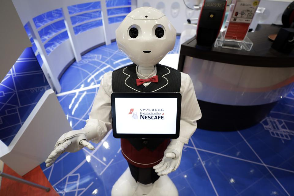 A SoftBank Group Corp. Pepper humanoid robot stands during a media preview of the human-less cafe inside Nestle SA's Nescafe coffee shop in the Harajuku district of Tokyo, Japan, on Thursday, Nov. 16, 2017. Kiyoshi Ota/Bloomberg