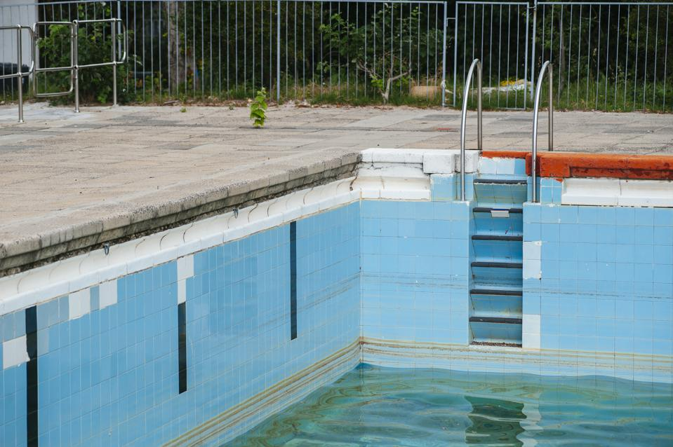 Blue-tiled swimming pool with very little water
