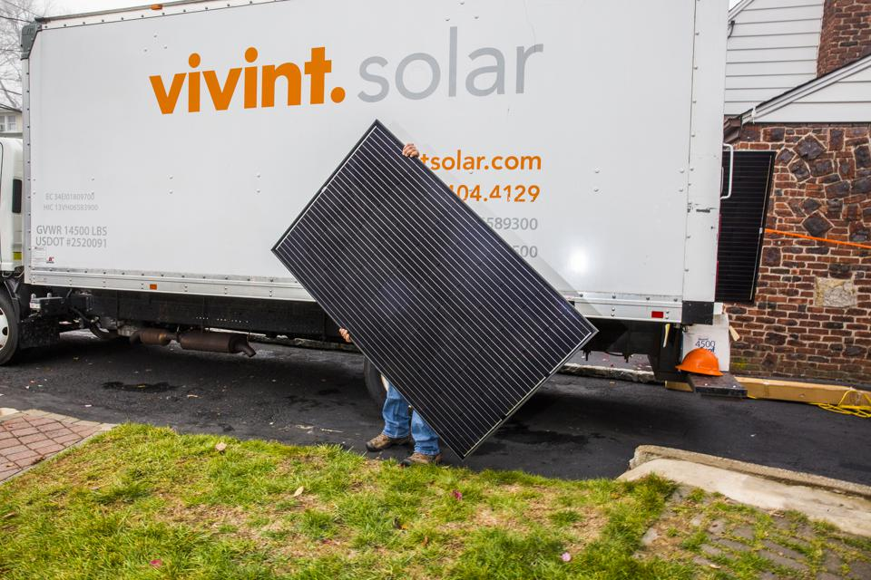 A worker moves a solar panel during a home installation in Bergenfield, New Jersey