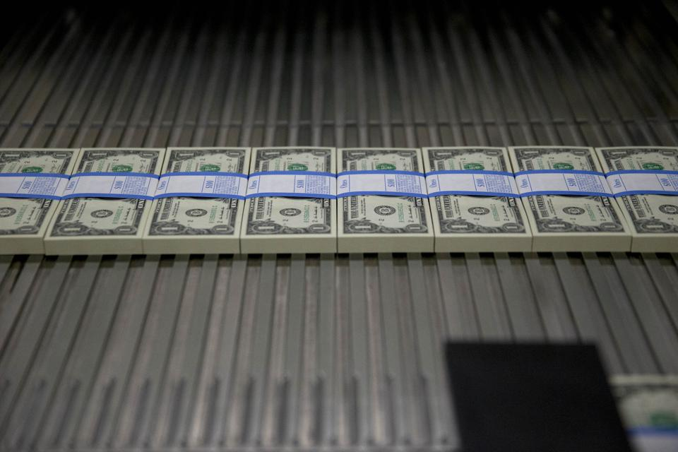 One dollar notes travel through a large examining packaging equipment machine