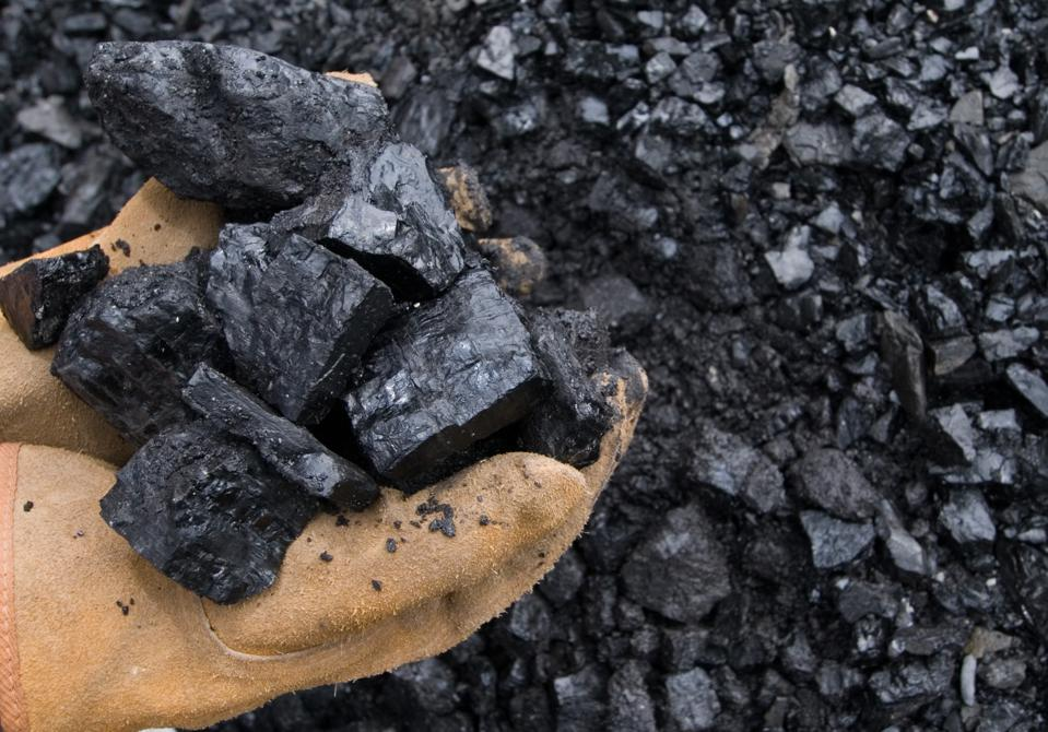 A worker displays a handful of coal