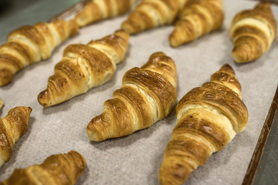 Freshly baked croissants sit on a tray inside a supermarket
