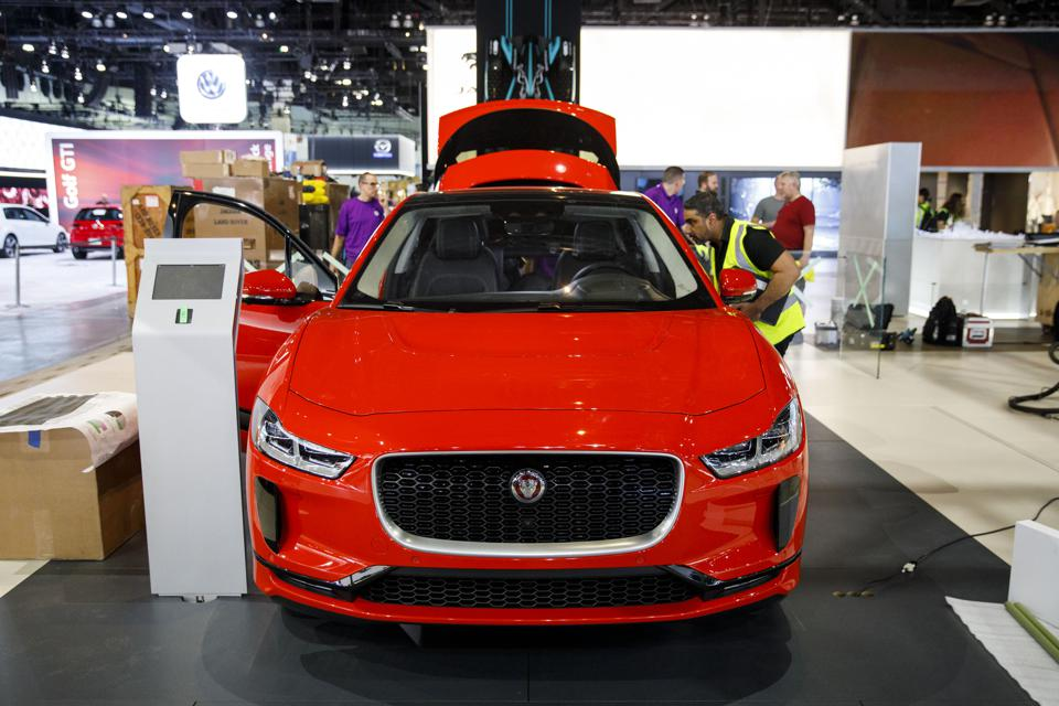 Workers inspect a Jaguar i-Pace electric vehicle at the Jaguar Land Rover Automotive Plc booth during preparations for AutoMobility LA ahead of the Los Angeles Auto Show on November 26, 2018.