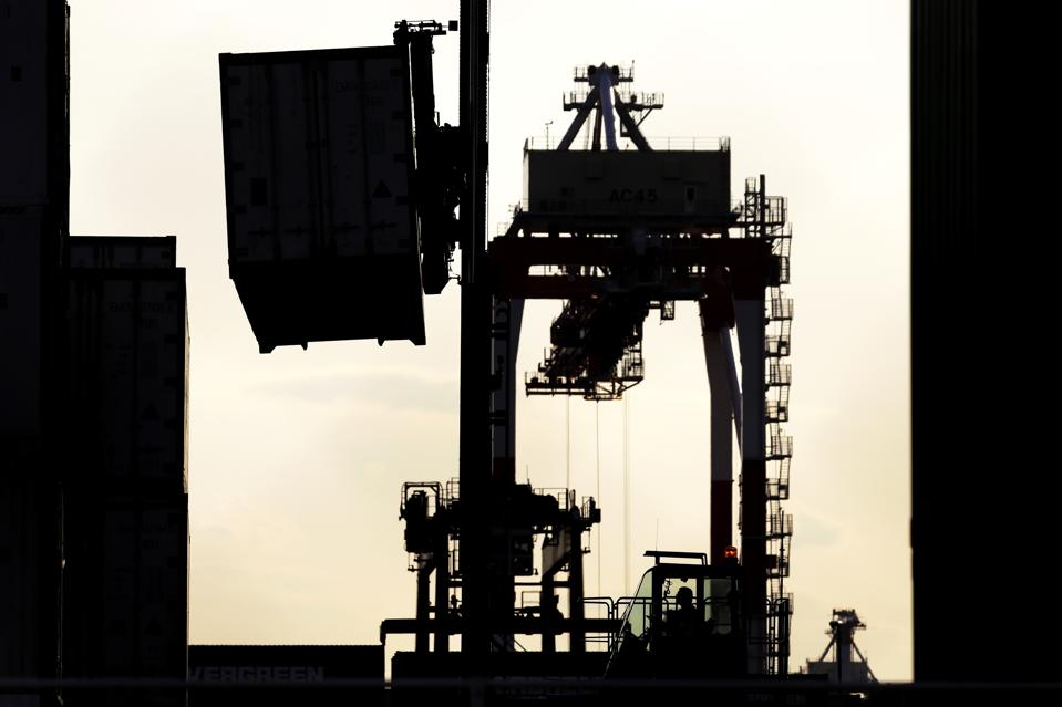 A container handler is silhouetted as it moves a shipping container