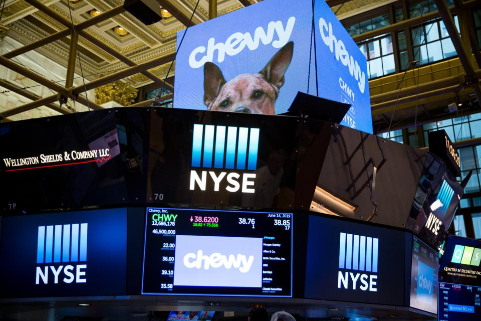 A photo of monitors at the New York Stock Exchange displaying the Chewy logo and Chewy images on the day of Chewy's initial public offering on June 14, 2019.