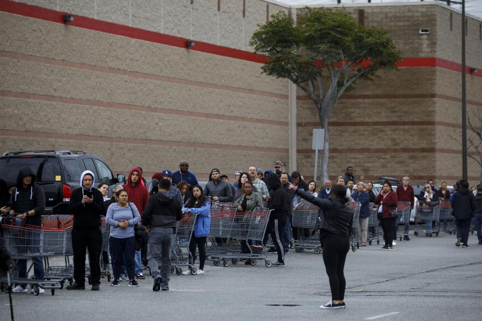An employee directs shoppers as they wait in line to enter a Costco in Hawthorne, California.