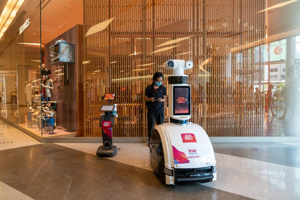 A 5G patrolling robot scans for shoppers temperatures and reports unmasked visitors.