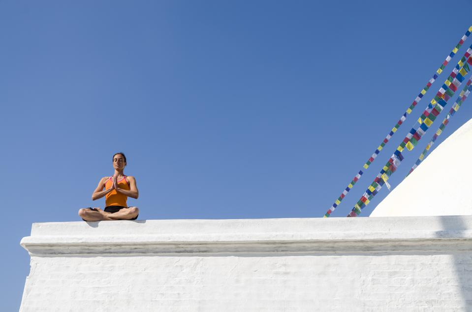 Young woman practicing yoga at Boudnath Stupa, showing the...