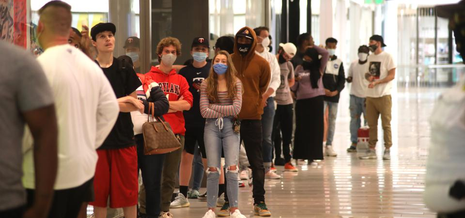 A line of shoppers wearing masks and waiting to get inside a store at the Mall of America/