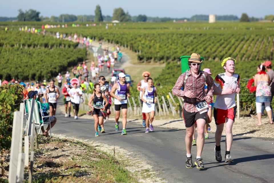 runners competing through vineyards at the Marathon de Medoc in Bordeaux, France