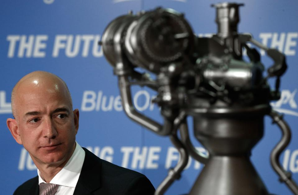 Blue Origin founder Jeff Bezos appears with a rocket engine at a press conference.