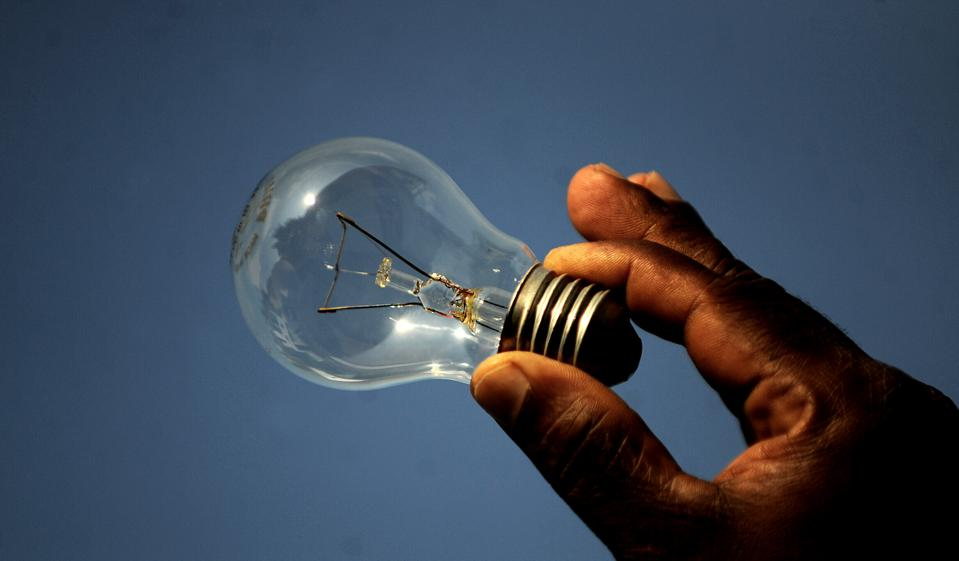 A hand holding an old-fashioned light bulb