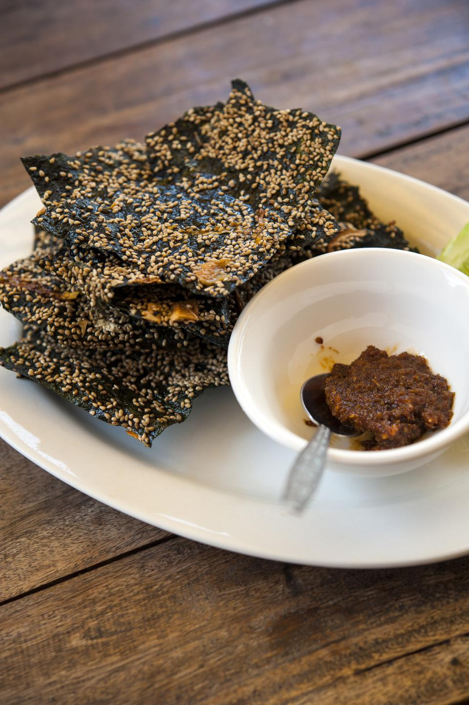 A plate of crispy river weed ″crackers″ with a bowl of jeow bong chili paste