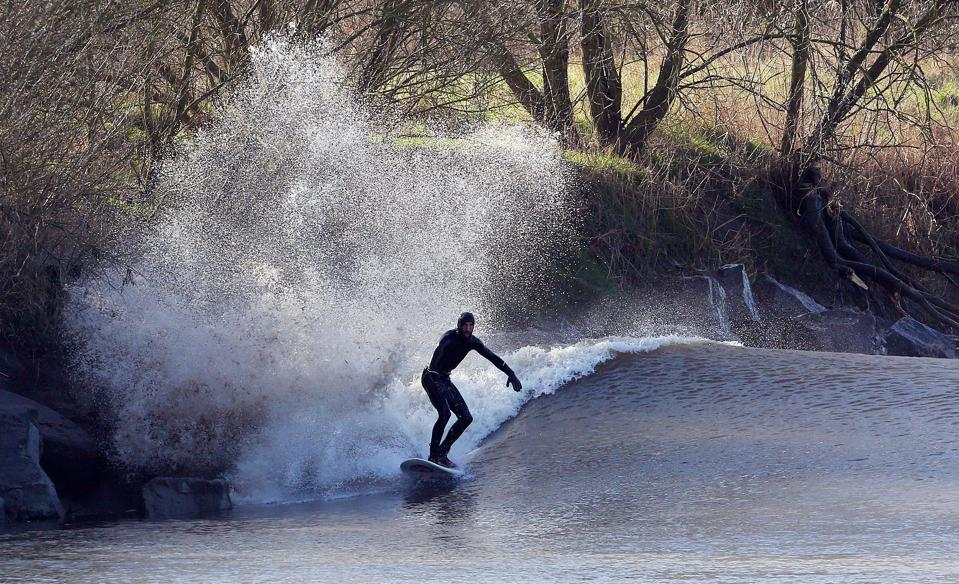 A surfer takes the wave of the tidal bore on the River Severn at Minsterworth in Gloucestershire, South West England on March 21, 2015. The Severn bore is a 'supertide' phenomenon on the River Severn.