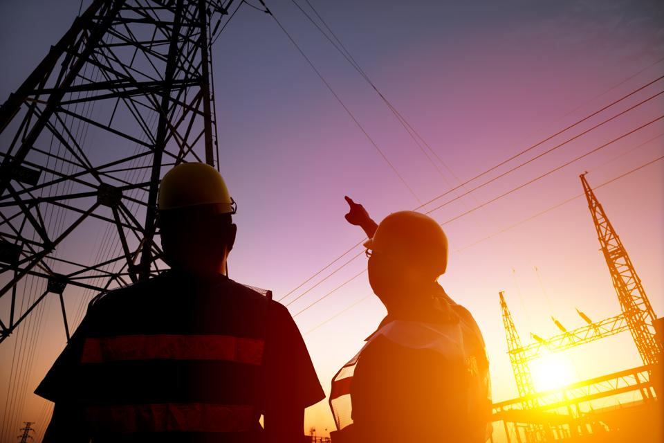 two worker watching the power tower and substation
