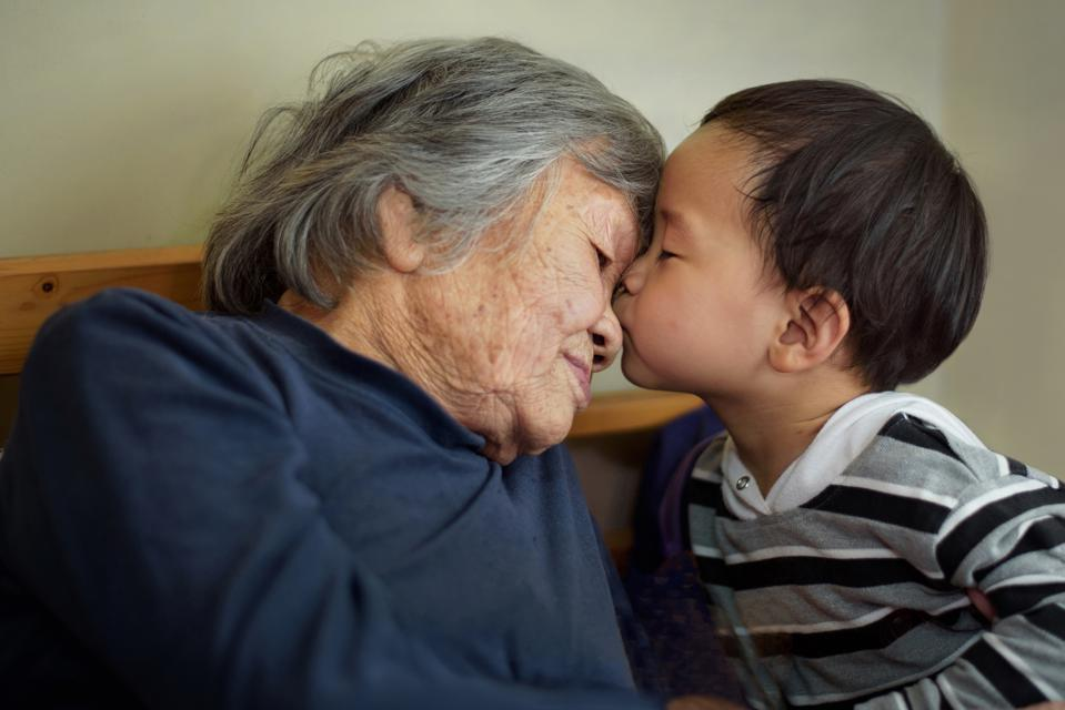 Asian little boy kissing grandmother