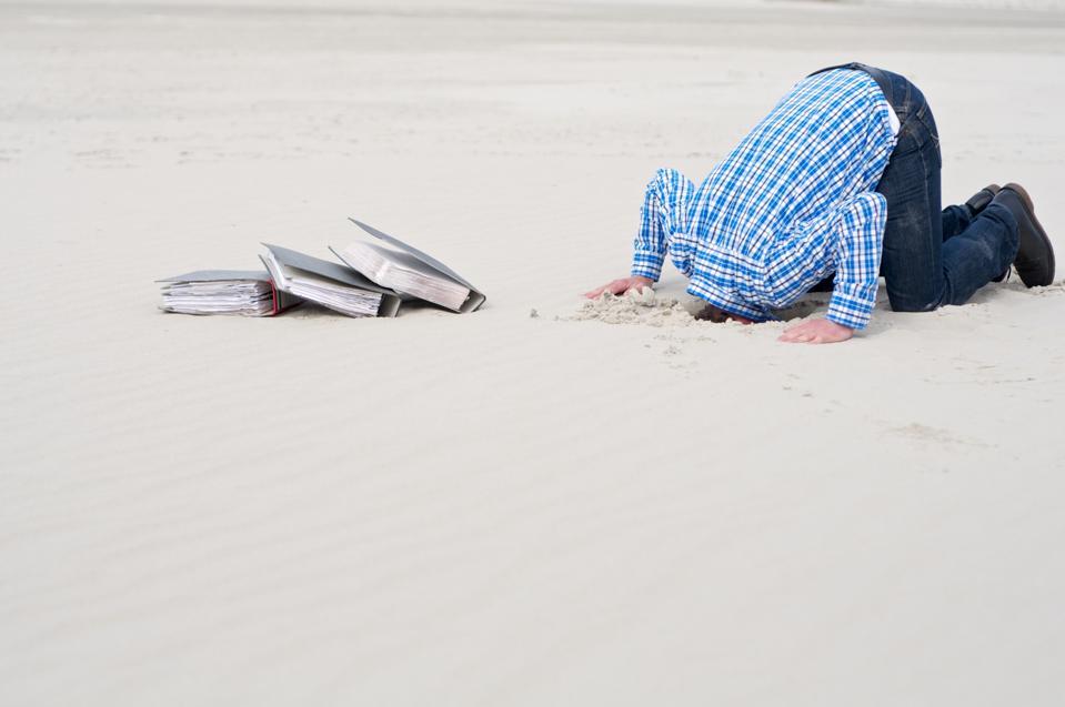 office worker hiding head in sand