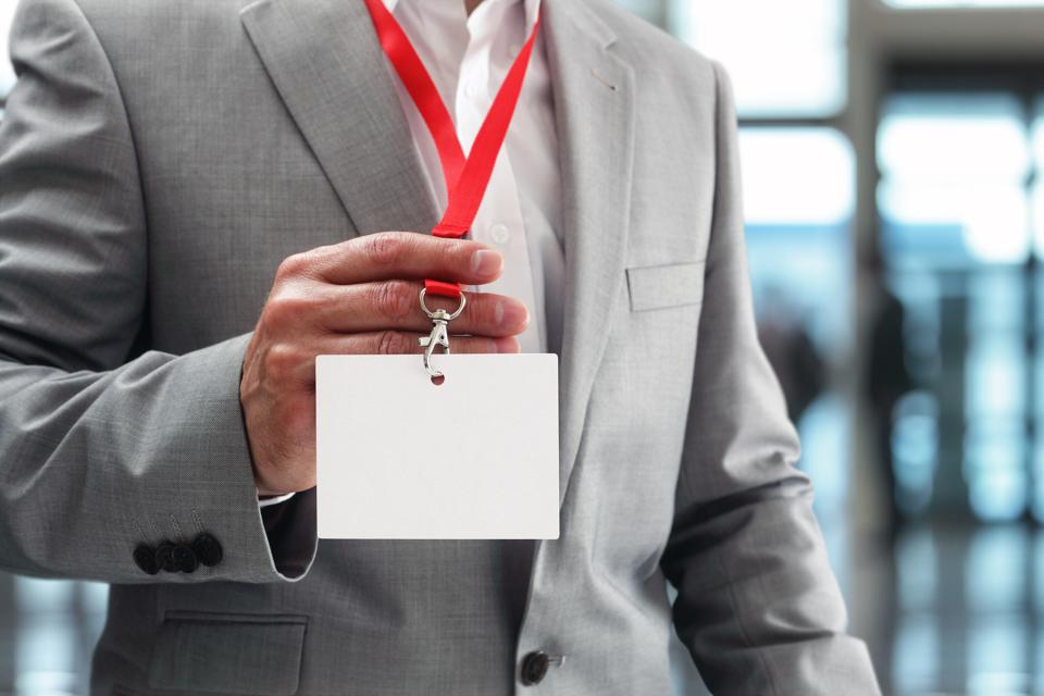 Businessman holding trade show badge