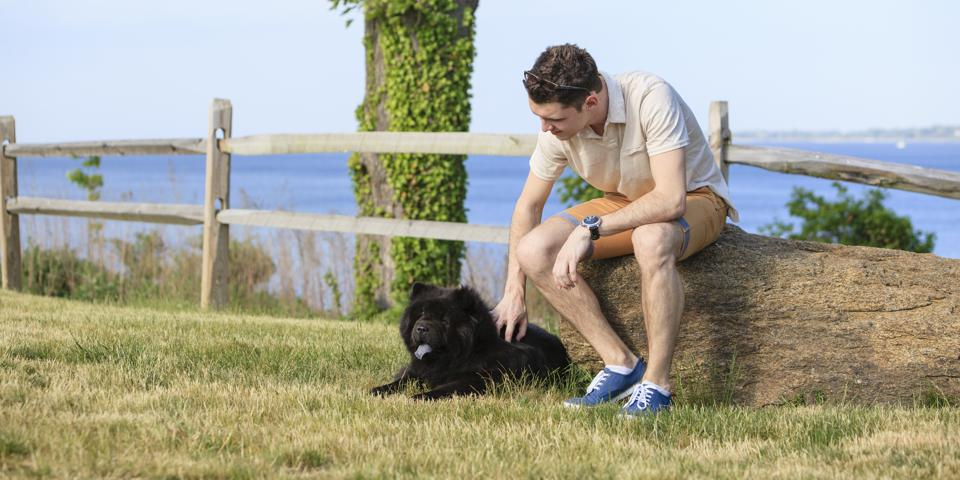 Young man and the black Chow Chow dog relaxing outdoor