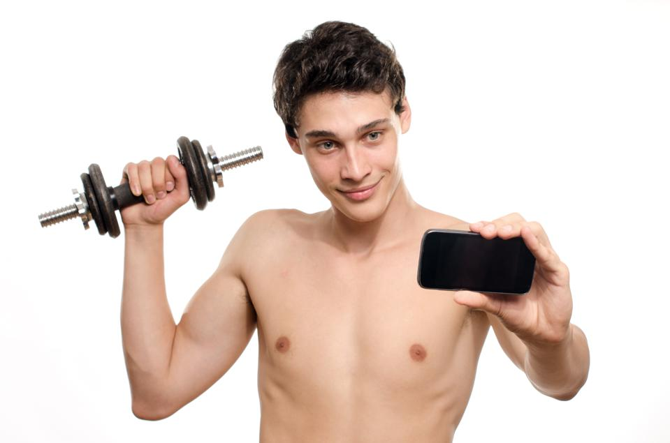 Skinny man taking selfie with phone while training bicep muscle