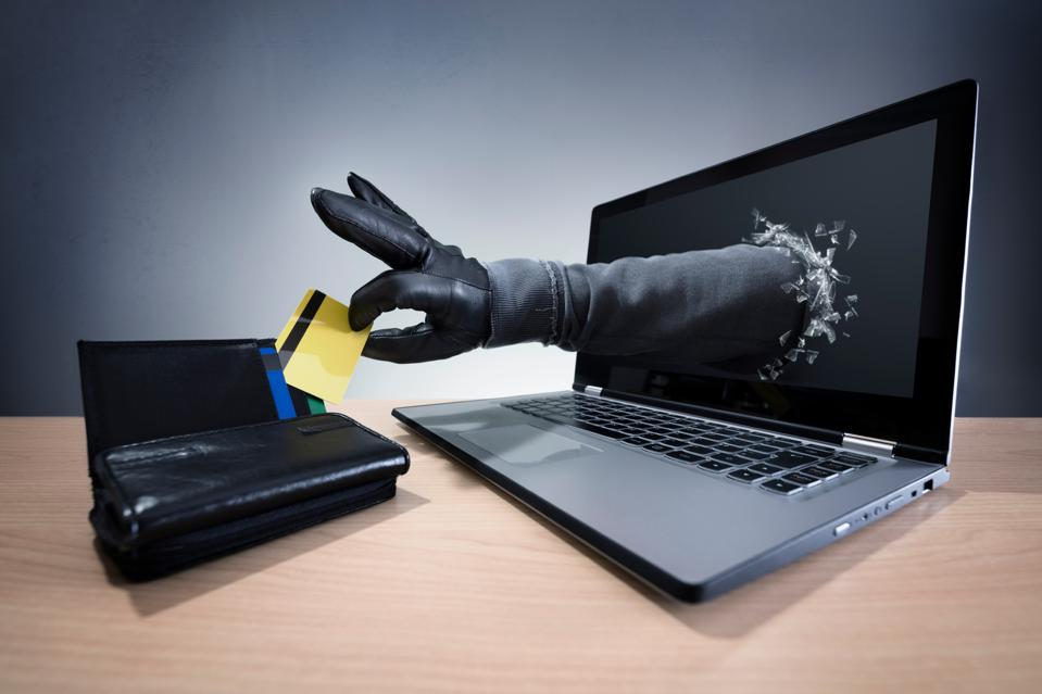 A gloved hand reaches out from a laptop screen to steal a credit card from a purse
