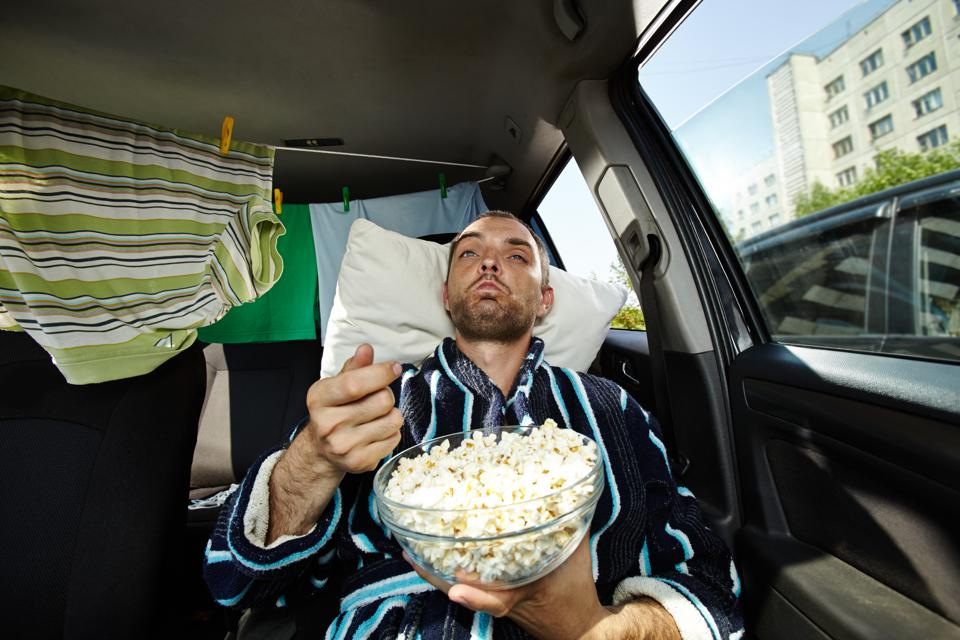 Man wearing bathrobe eating popcorn in car, drying rack with clothes behind him
