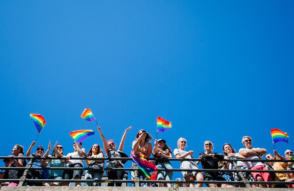 People with rainbow flags watch Stockholm Gay Pride parade