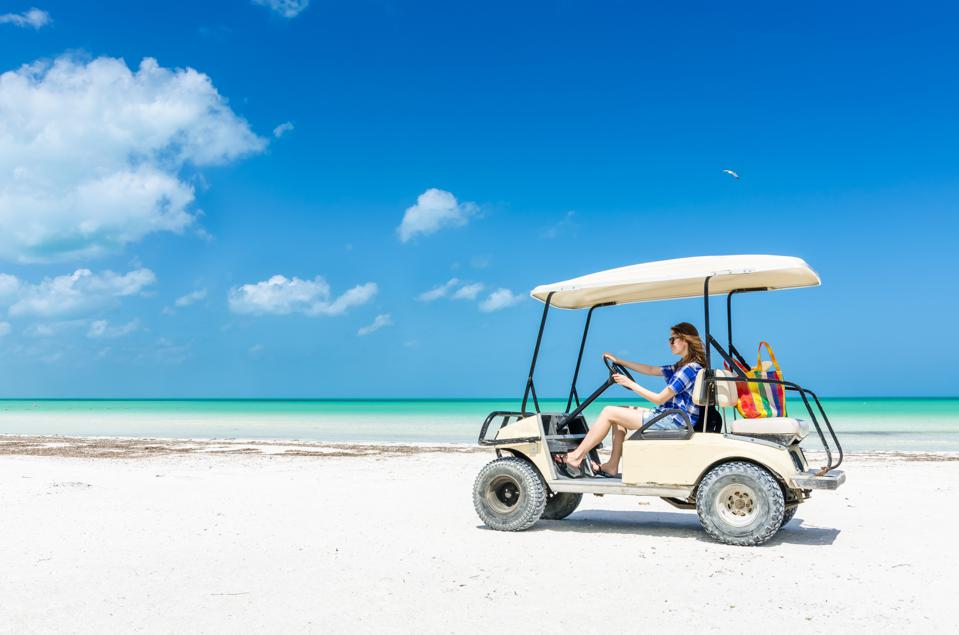 Young woman driving golf cart along tropical beach during vacation