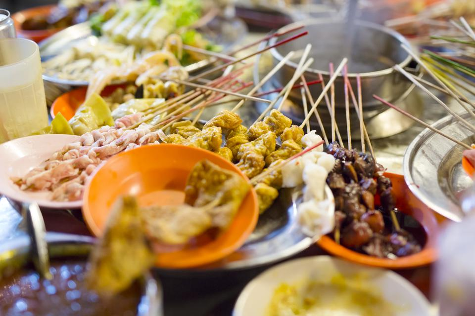 Satay, a popular hawker stall food, ready to be served with peanut and soy sauces