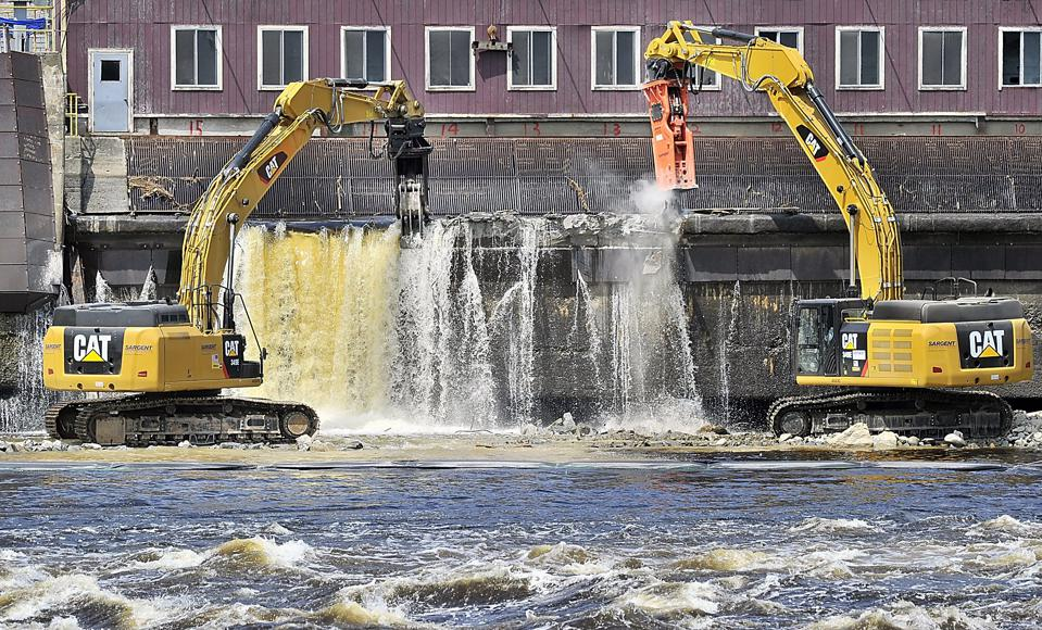 On Monday, July 22, 2013, using excavators, construction workers breach the Veazie Dam in preparatio