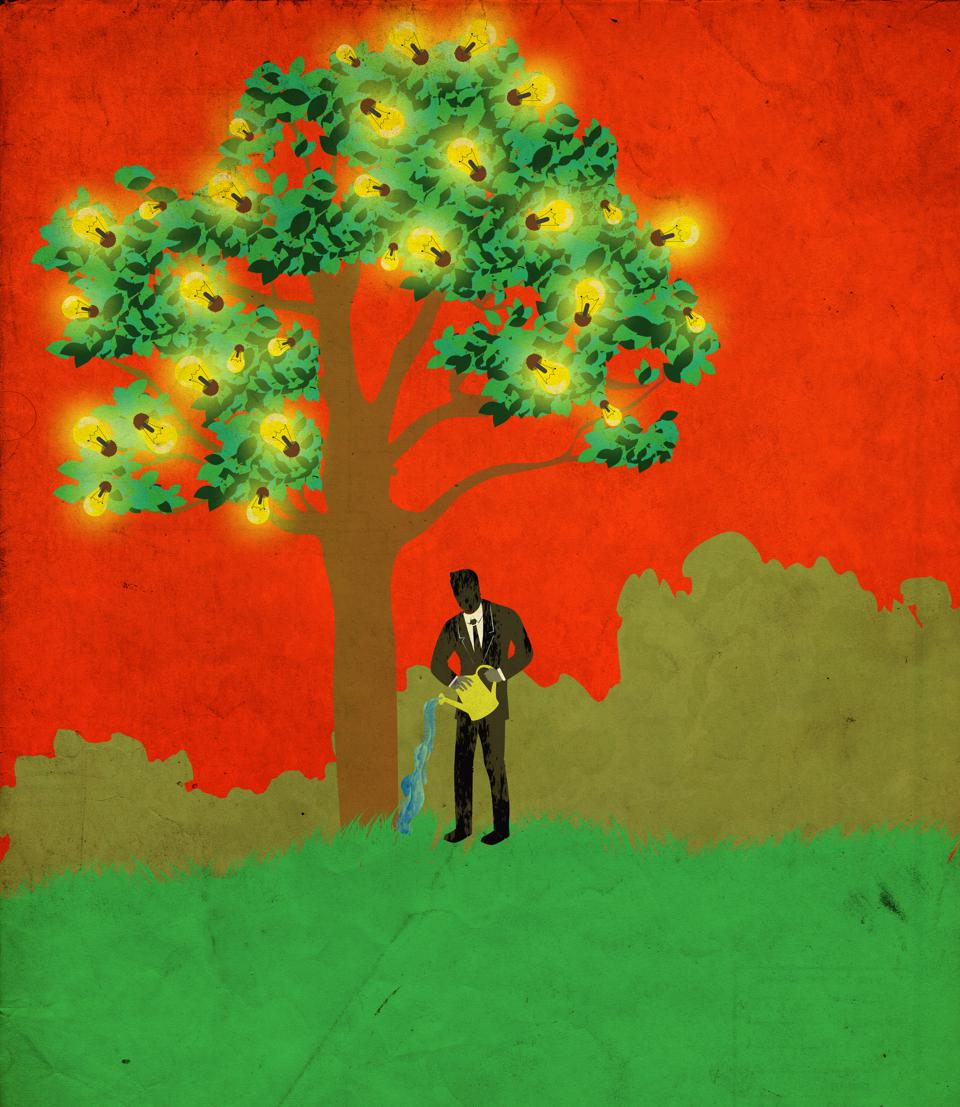 Conceptual shot of businessman watering tree with glowing light bulbs representing growth of new ideas
