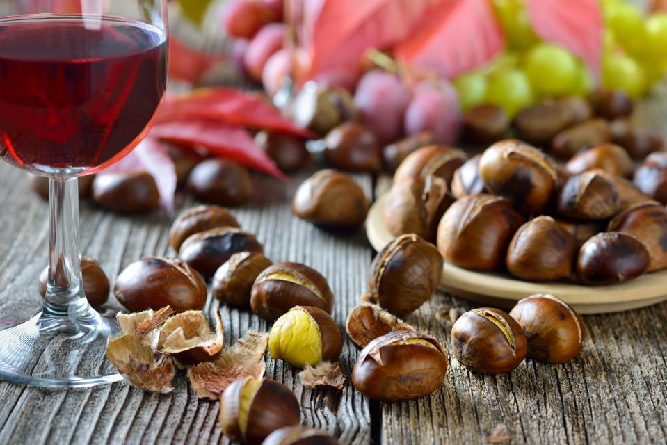 Chestnuts and wine Roasted chestnuts with South Tyrolean red wine on an old wooden table, wine grapes in the background