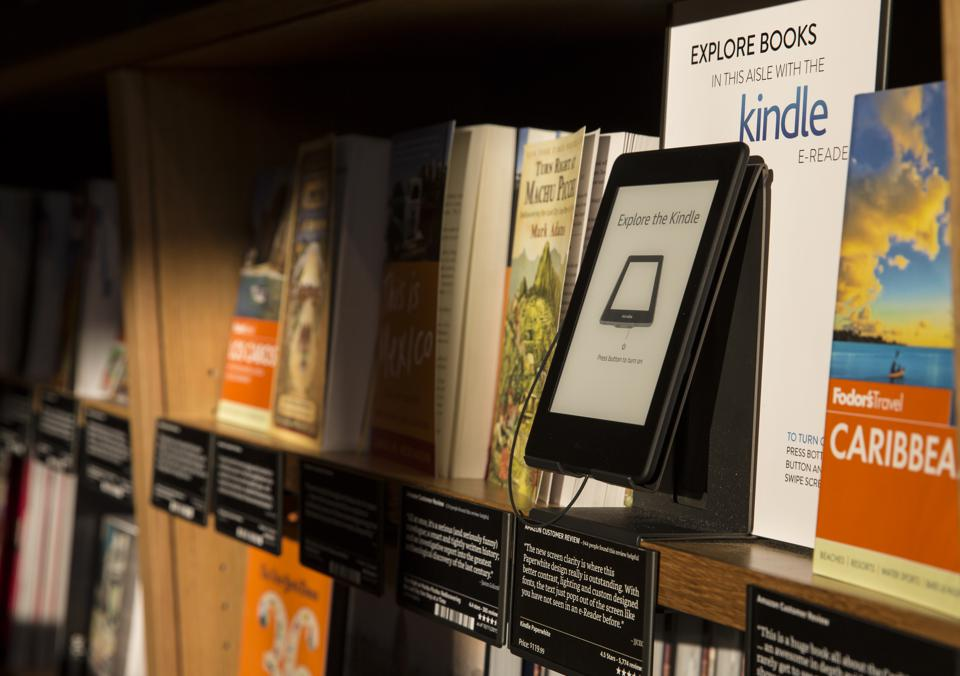 a bookshelf in a bookstore with books and a Kindle sitting on it