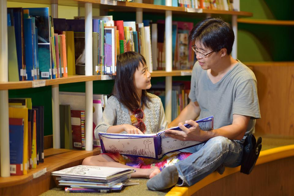 Asian girl and father reading in library