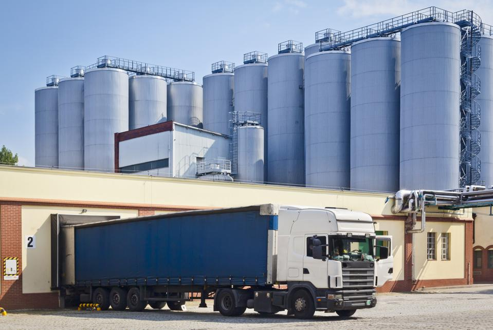 Warehouse building with fright truck and steel silos in the brewery, Tychy, Poland