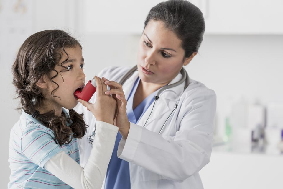 Doctor helping patient use inhaler in office