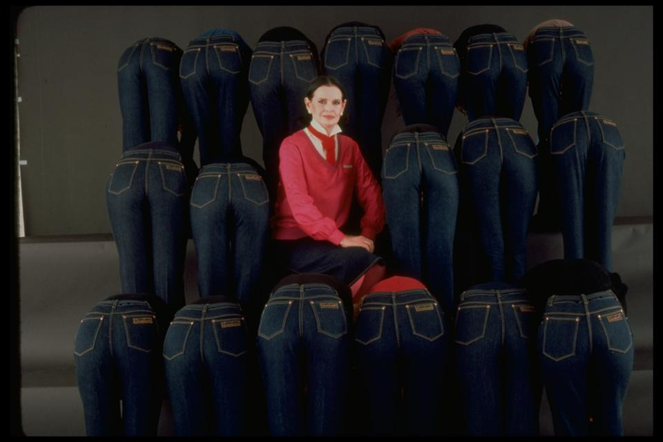 Gloria Vanderbilt sits amidst models bending over to accent the rear of her designer jeans