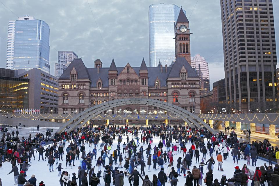Holiday crowd ice-skating in Toronto square at dusk