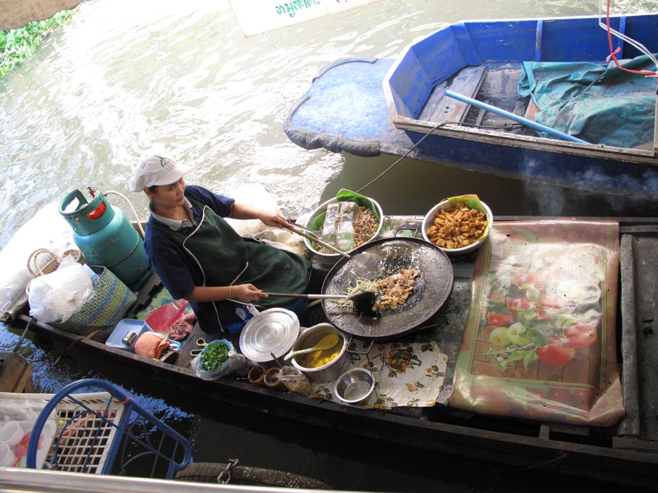 Man in a small, flat boat cooking stir fry surrounded by ingredients